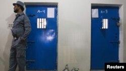 Сотрудник тюрьмы стоит у дверей камер в афганском городе Лашкаргах.