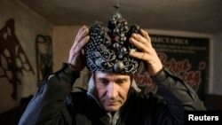 Blacksmith Viktor Mikhalev wears a metal crown made in the likeness of the Imperial Crown of Russia at his shop in Donetsk in eastern Ukraine. Mikhalev makes his handicrafts from the remains of ammunition left behind in the fighting between pro-Russian separatists and Ukrainian government forces. (Reuters/Maxim Shemetov)