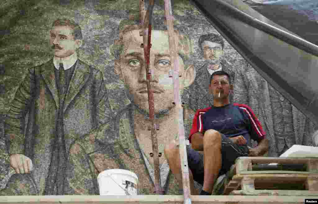 A worker smokes a cigarette in front of a mosaic with an image of Gavrilo Princip, the Bosnian-Serb assassin whose actions helped precipitate the outbreak of World War I, in Andricgrad village near Visegrad in Bosnia-Herzegovina on June 23. (Reuters/Djordje Kojadinovic)