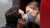 Поцілунок через маски перед тим як рушить потяг. Дівчина повертається із Брюсселя у Париж у перший день послаблення карантинних заходів у Бельгії (REUTERS/Yves Herman). Травень 2020 року