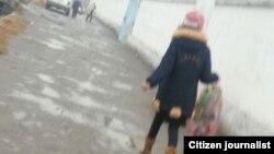 Кокандская школьница несет в школу собранные в мусорках баклажки.