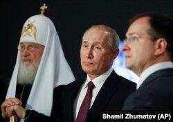 Președintele rus Vladimir Putin (mijloc), Patriarhul Kiril (stânga) și Vladimir Medinski (dreapta), în vizită la Moscova pentru o expoziție despre al Doilea Război Mondial, cunoscut în Rusia drept Marele Război Patriotic.