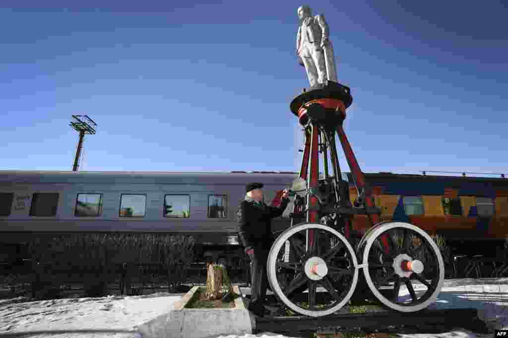 A railroad museum employee shows a wheeled monument to the founder of the Soviet state, Vladimir Lenin, in Moscow. It is one of 16 such monuments created in 1925, one year after Lenin's death, by Moscow's railroad workers to promote his ideas in remote areas. (AFP/Alexander Nemenov)