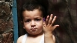 A Pakistani child shows his marked finger after receiving the polio vaccine in Lahore, Pakistan, on April 24.