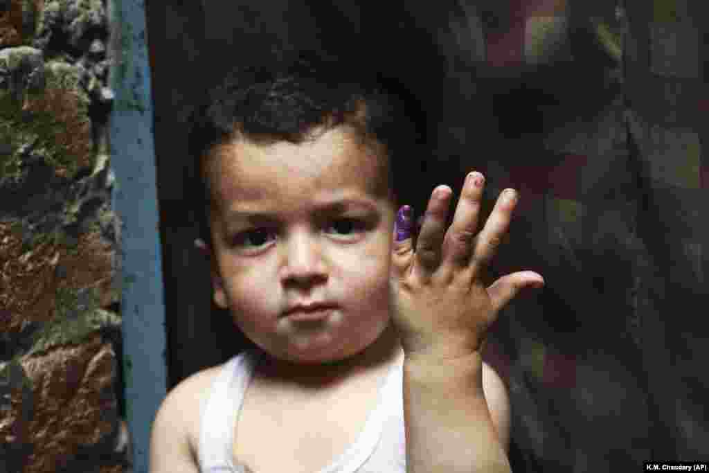 A Pakistani child shows his finger after being marked that he had received the polio vaccine in Lahore, Pakistan, on April 24. A Pakistani health official says two new polio cases have been reported in the country's northwest despite efforts against the crippling disease. Meanwhile, Pakistani health officials suspended the campaign following the killings in less than a week of a health worker and two policemen escorting vaccination teams. (AP/K.M. Chaudary)
