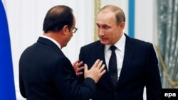 Russian President Vladimir Putin (right) and French President Francois Hollande talk after a press conference following their talks at the Kremlin in Moscow in November 2015.