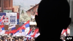 An ethnic Serbian boy looks at people demonstrating against the accord on the normalization of relations between Serbia and Kosovo in the ethnically divided town of Mitrovica on April 22.