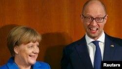 Канцлер Германии Ангела Меркель (слева) и премьер-министр Украины Арсений Яценюк на форуме в Берлине. 23 октября 2015 года.