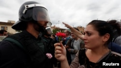 A woman gives a carnation to a Spanish Civil Guard officer outside a polling station in Sant Julia de Ramis, Spain on October 1, 2017.
