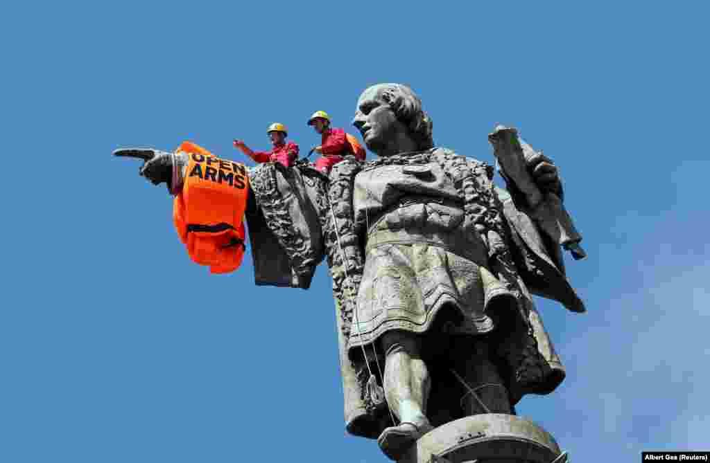 Актывісты гішпанскай дабрачыннай арганізацыі Proactiva Open Arms надзяваюць на статую Калюмба ратавальную камізэльку пасьля таго, як іх судна прыбыла ў барсэлёнскі порт з уратаванымі ля берагоў Лібіі мігрантамі. (Reuters/Albert Gea)