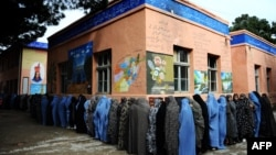 Afghan women queue outside a school to vote in presidential and local elections in the northwestern city of Herat on April 5. Female participation in the polls was far higher than expected.