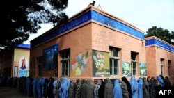 Afghan women queue outside a school to vote in presidential elections in the western city of Herat.