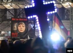 Участники антиисламской демонстрации в Лейпциге несут плакат с изображением канцлера ФРГ Ангелы Меркель в мусульманском платке