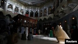FILE: A woman clad in burqa walks in the hallway of the tomb of Sufi saint Syed Usman Marwandi, also known as Lal Shahbaz Qalandar, in Sehwan Sharif, in Pakistan's southern Sindh Province.