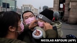 Люди в защитных масках на железнодорожном вокзале в Пекине. 27 января 2020 года.
