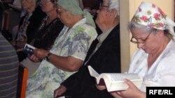 Верующие в церкви с библией в руках. Иллюстративное фото.