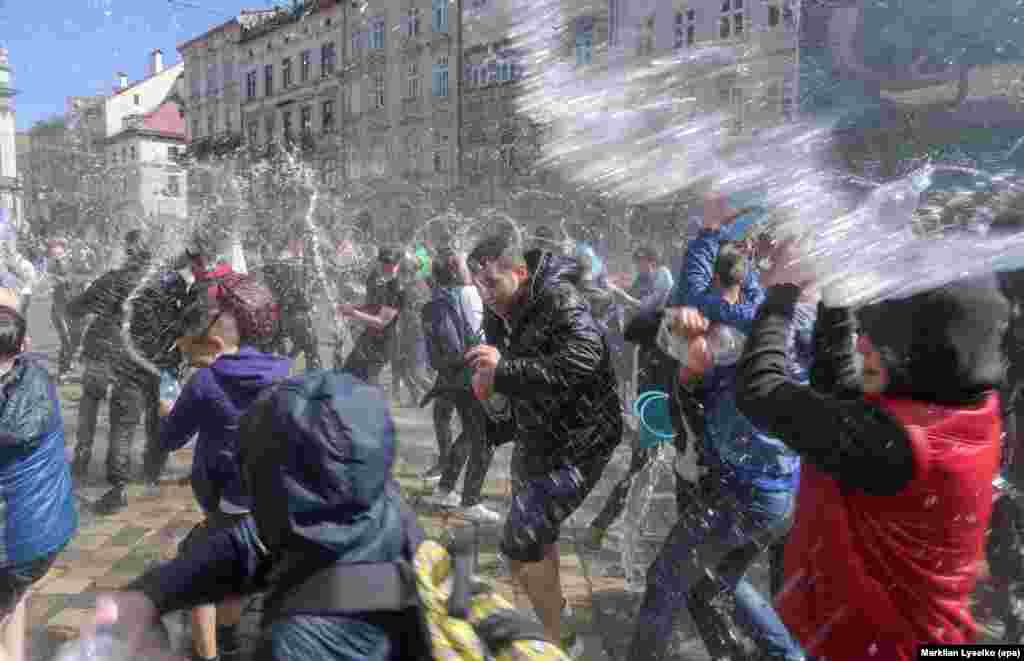 Ukrainians pour water on each other on a street in the western Ukrainian city of Lviv. The custom is an ancient spring rite of cleansing that takes place on the first Monday after Orthodox Easter. (epa/Markiian Lyseiko)