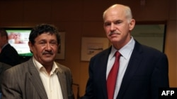 Gresiýanyň premýer-ministri George Papandreou (sagda) Liwiýanyň daşary işler ministriniň orunbasary Abdelati al-Obeýdi bilen duşuşýar, Afiny, 2011-njy ýylyň 3-nji apreli.