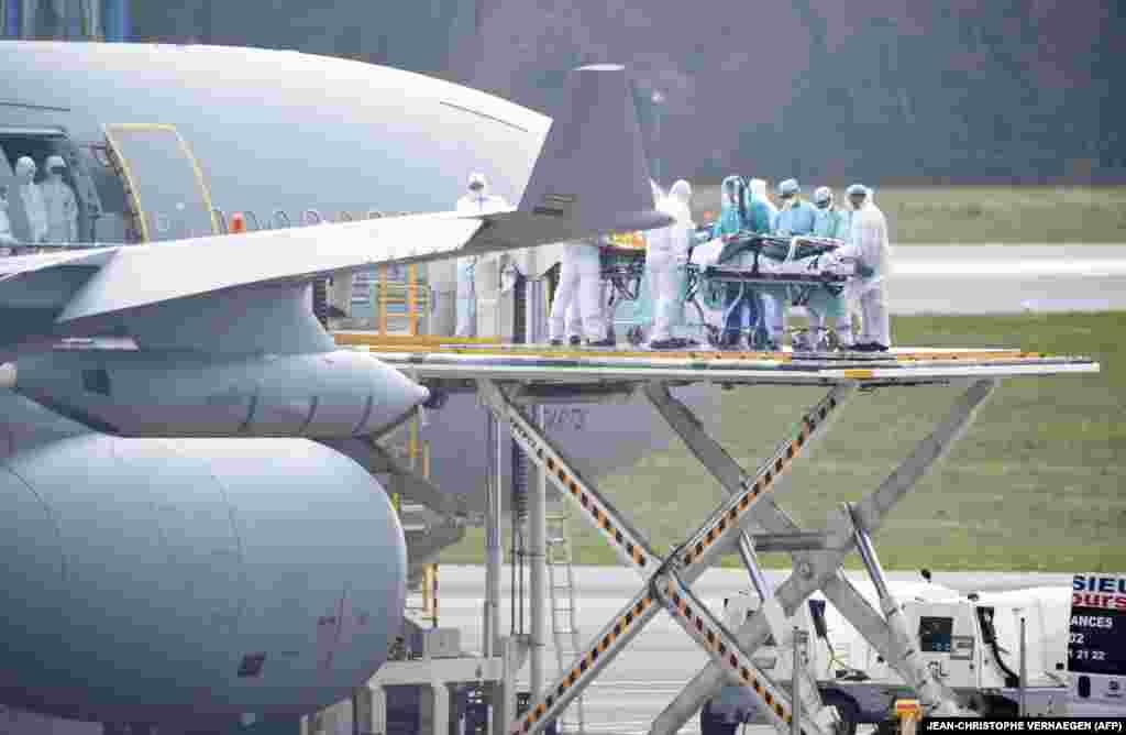 """Медицински персонал качи пациенти, заразени с коронавирус, на самолет на френските военно-въздушни сили на 3 април на летището """"Финдел"""" в Люксембург."""