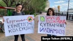 Жители столицы — фрилансер Бэлла Орынбетова и графический дизайнер Муратбек Каримов — показывают свои плакаты для журналиста. Нур-Султан, 4 августа 2019 года.