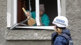 A member of the OSCE walks past a local resident, who removes debris inside a house damaged during recent fighting between Ukrainian forces and Russia-backed separatists in Luhansk in eastern Ukrainie.