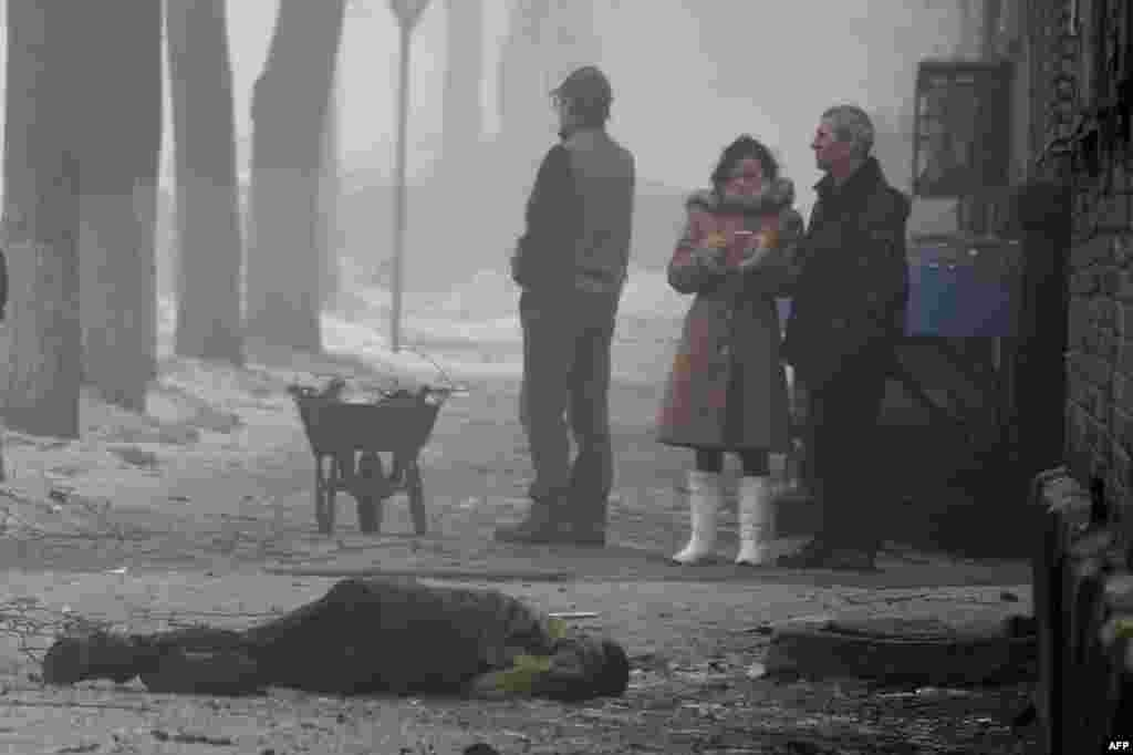 People stand beside the body of a man killed after a shell hit a residential area, killing two civilians, in Donetsk's Kyibishevsky district.
