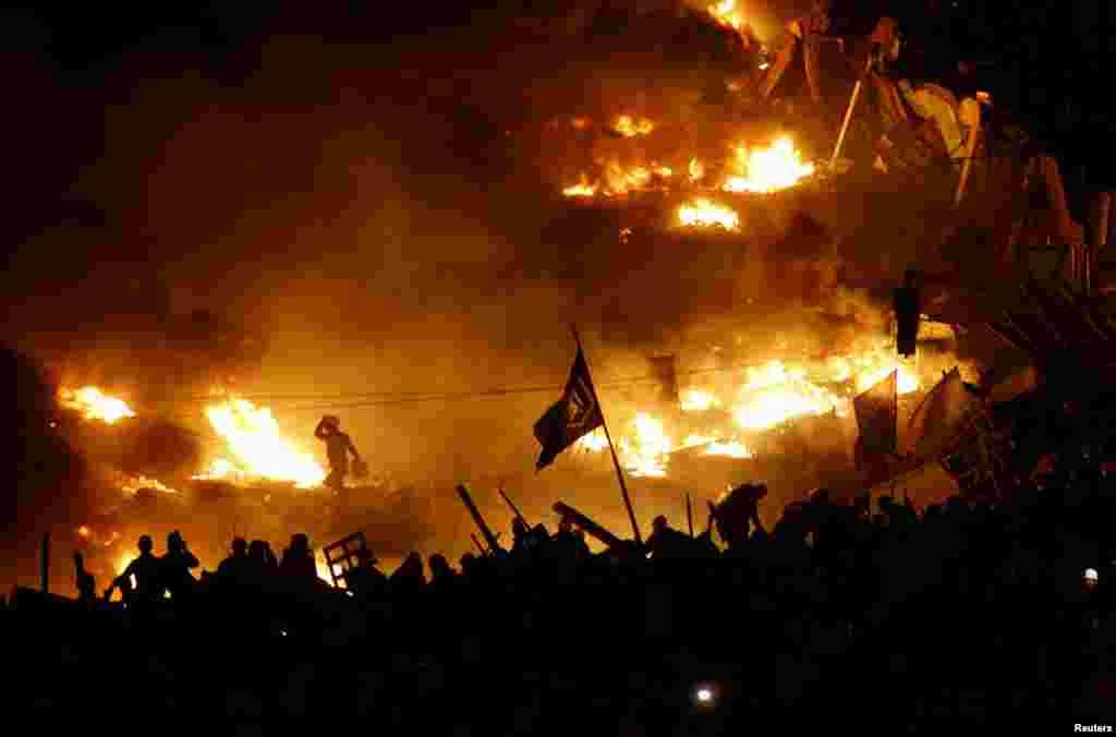 19 лютого.Протестуючі біля палаючих барикад на майдані Незалежності