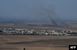 Дым вблизи афганской военной базы во время боев между талибами и афганскими силами безопасности в провинции Кундуз. 1 октября 2015 года.