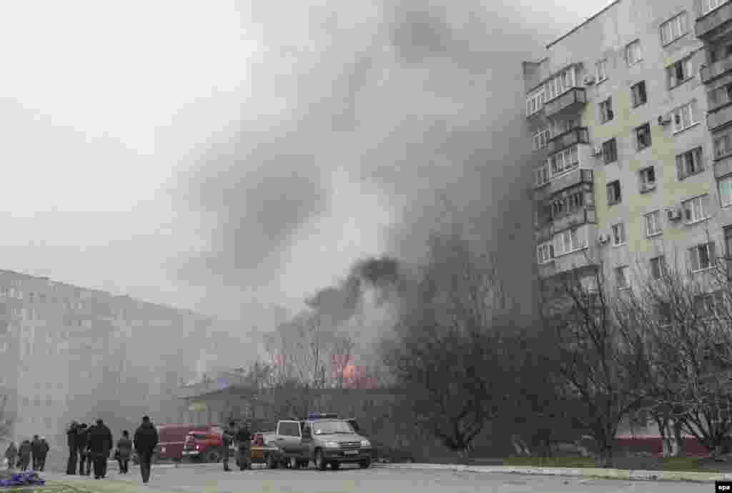 Smoke and flames rise above a burning building in Mariupol.