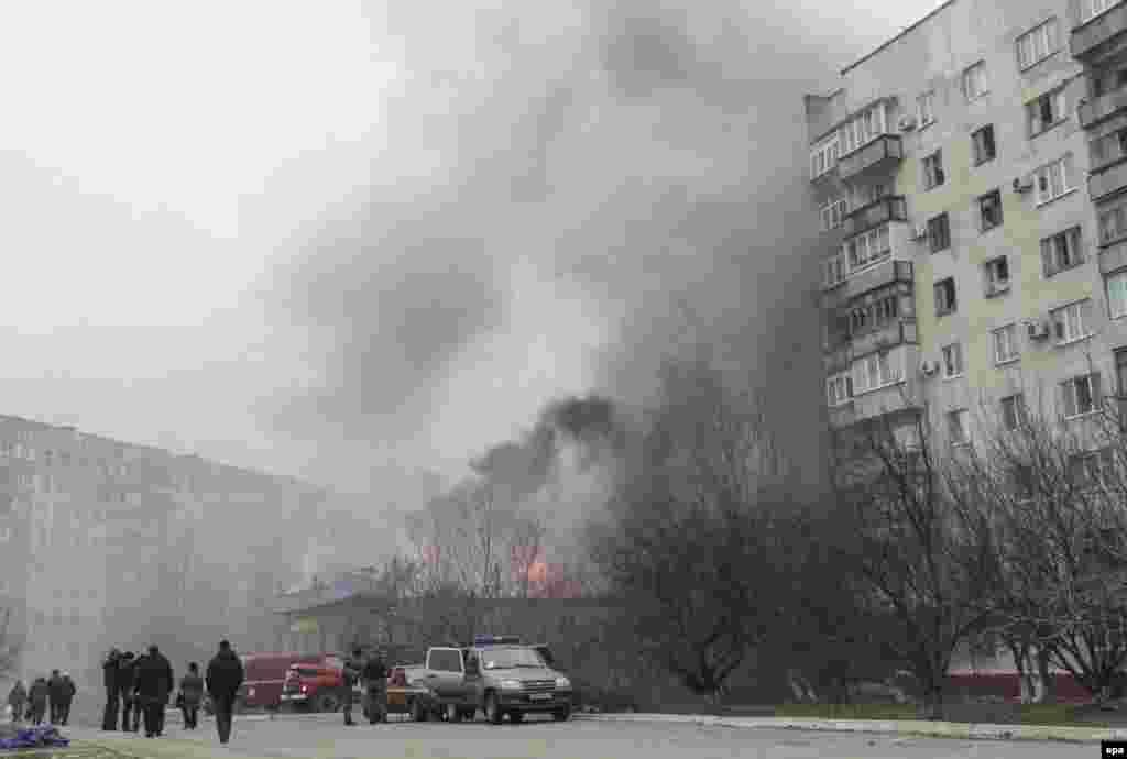 24 січня 2015 року. Пожежа та дим над будівлею внаслідок обстрілусхідних житлових кварталів Маріуполя. 24 січня від обстрілу установками залпового вогню загинула 31 людина, понад 100 осіб були поранені. Обстріл, як визначила спеціальна моніторингова місія ОБСЄ, вівся з території, підконтрольній угрупованню «ДНР», що визнане в Україні терористичним. За даними СБУ, Маріуполь обстріляларосійська артилерія