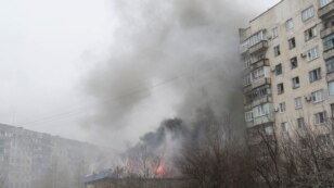Ukraine -- Smoke and flames rise above a burning building after shelling in the eastern Ukrainian city of Mariupol, 24 January 2015.