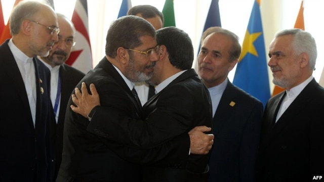 Iranian President Mahmud Ahmadinejad (right) embraces his Egyptian counterpart, Muhammad Morsi, as they attend the opening of a Nonalligned Movement summit in Tehran on August 30