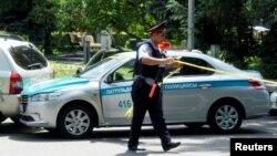 Qurshovga olingan joyda ishlayotgan politsiya zobiti, Olmaota, 2016 yil 18 iyuli.