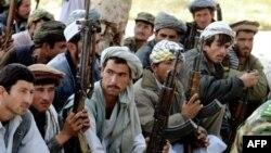 Militiamen wait to turn in their weapons.