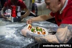 Павал робіць піцу хуткімі спрактыкаванымі рухамі