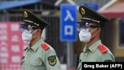 """""""Жаңа вирус ошағы"""" деп танылған """"Синьфади"""" ірі базардың кіре берісінде тұрған полиция қызметкерлері. Пекин, 13 маусым 2020 жыл."""