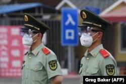 Китайська поліція в масках біля зачиненого ринку «Сінфаді» в Пекіні