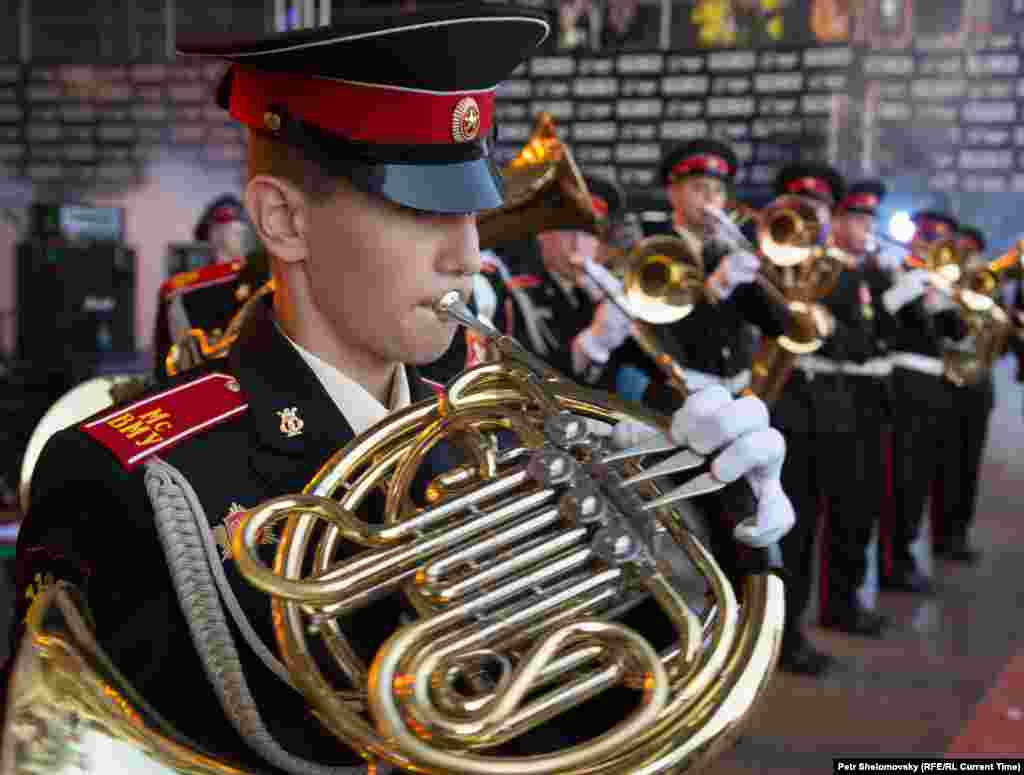 Far from the main stage, military cadets play in a marching band.