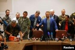 Окупований Донецьк, 22 липня 2014 року. Олександр Бородай (посередині), громадянин Росії, тодішній ватажок угруповання «ДНР», що визнане в Україні терористичним. На фотографії бойовики передають малайзійським експертам чорні скриньки «Боїнга» рейсу MH-17, який був збитий російською зенітно-ракетною установкою «Бук»