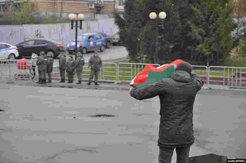 Чара беткәч татар активисты аркасындагы байракны җыеп кайтып бара.