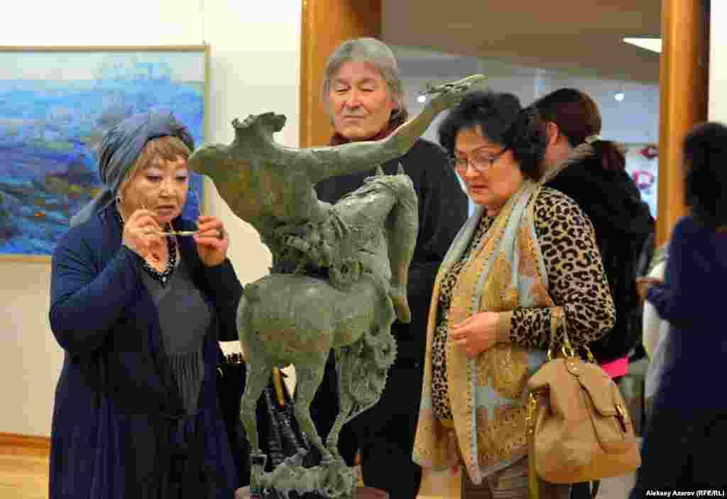 Гости и участники выставки рассматривают произведение «Джайляу» (бронза, металл) известного скульптора Алибека Мергенева, в творчестве которого синтезируется опыт европейской и восточной пластической традиции.
