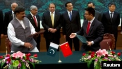 File photo of Pakistani Prime Minister Nawaz Sharif (center L) and Chinese Premier Li Keqiang (center R) observe a signing ceremony.