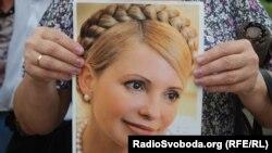 Юлия Тимошенконың суретін ұстап тұрған адам. Көрнекі сурет.