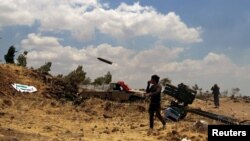 Free Syrian Army rebel fighters fire rockets towards government forces in the northern countryside of Quneitra in June this year.