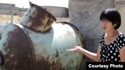 """Гульдар Мырзабаева, жительница микрорайона """"Нуртас"""" , показывает на бочку с водой. Шымкент, 20 августа 2010 года."""