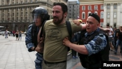 Police detain Dmitry Tsorionov, known by the nickname Dmitry Enteo, leader of the Orthodox group God's Will, after his supporters fought with gay-rights activists during an LGBT community rally in central Moscow on May 30.