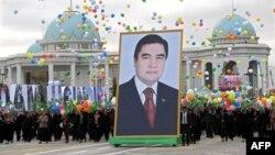 Türkmenistanda döwletiň guramaçylygyndaky baýramçylyk çärä gatnaşýan adamlar prezident Gurbanguly Berdimuhamedowyň portretini göterýär
