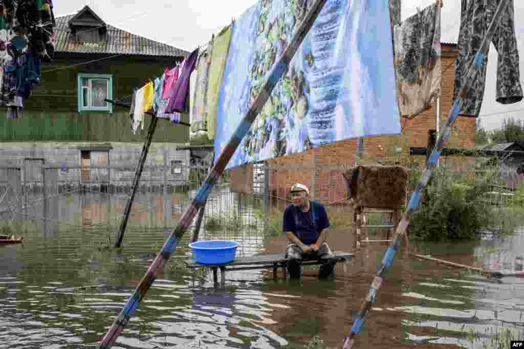 A man sits by a flooded street in the village of Bolshoi Ussuriysky near Khabarovsk.