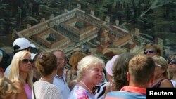 Turisti prolaze pored plakata na kojemu je prikaz Dioklecijanove palače, Split, fotoarhiv