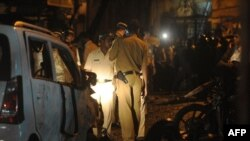 India -- Police officials inspect a bomb blast site at the Opera house area in Mumbai, 13Jul2011